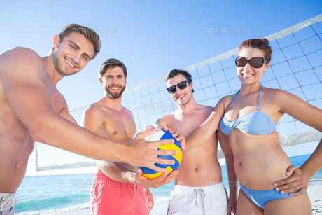 Group of friends holding volleyball and smiling at cameraの写真素材 [FYI00007038]