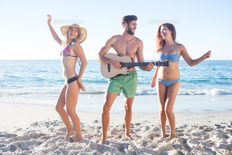 Handsome man playing guitar and his friends dancingの写真素材 [FYI00007060]