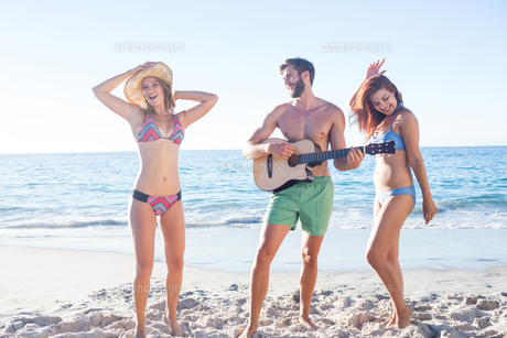 Handsome man playing guitar and his friends dancingの写真素材 [FYI00007061]