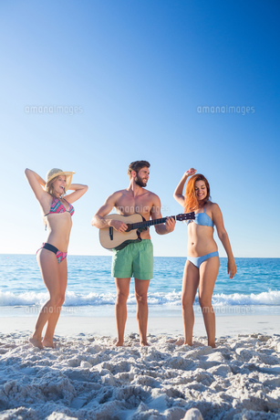 Handsome man playing guitar and his friends dancingの写真素材 [FYI00007067]