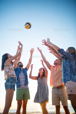 Happy friends throwing volleyballの写真素材 [FYI00007085]
