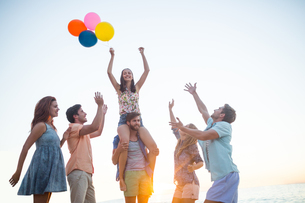 Happy friends dancing on the sand with balloonの写真素材 [FYI00007101]