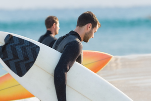 Two men in wetsuits with a surfboard on a sunny dayの写真素材 [FYI00007103]