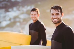 Two men in wetsuits with a surfboard on a sunny dayの写真素材 [FYI00007104]