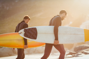 Two men in wetsuits with a surfboard on a sunny dayの写真素材 [FYI00007105]