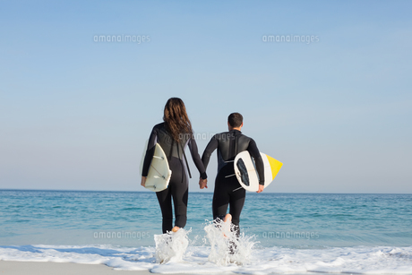 happy couple in wetsuits with surfboard on a sunny dayの写真素材 [FYI00007106]