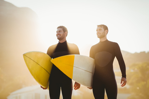 Two men in wetsuits with a surfboard on a sunny dayの写真素材 [FYI00007110]