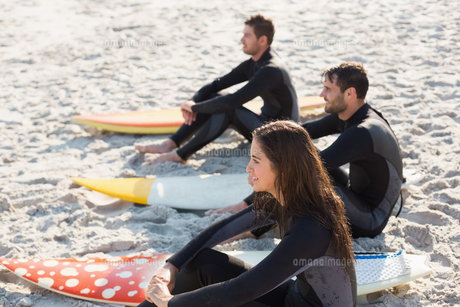 Group of friends on wetsuits with a surfboard on a sunny dayの写真素材 [FYI00007112]