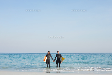 happy couple in wetsuits with surfboard on a sunny dayの写真素材 [FYI00007113]