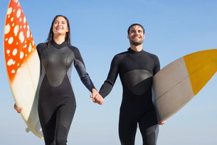 happy couple in wetsuits with surfboard on a sunny dayの写真素材 [FYI00007115]