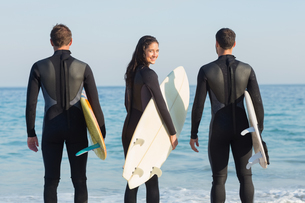 Group of friends on wetsuits with a surfboard on a sunny dayの写真素材 [FYI00007119]