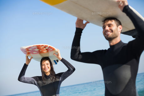 happy couple in wetsuits with surfboard on a sunny dayの写真素材 [FYI00007120]