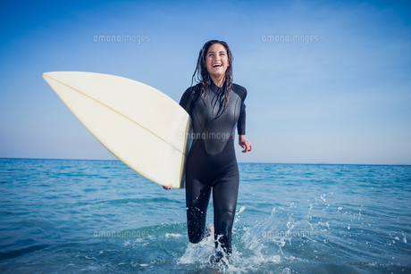 woman in wetsuit with a surfboard on a sunny dayの写真素材 [FYI00007121]