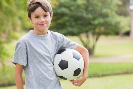 Smiling boy holding a soccer ball in the parkの写真素材 [FYI00007162]