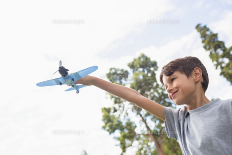 Boy playing with a toy plane at parkの写真素材 [FYI00007168]