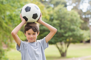 Smiling boy holding a soccer ball in the parkの写真素材 [FYI00007169]