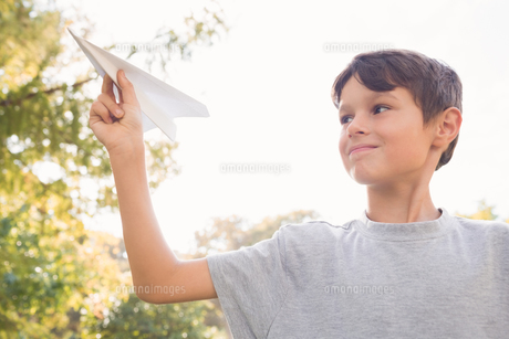 Smiling boy with paper plane in the parkの写真素材 [FYI00007172]