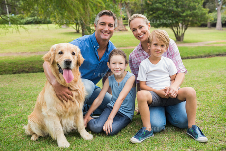 Happy family smiling at the camera with their dogの素材 [FYI00007195]