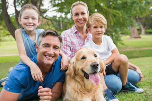 Happy family smiling at the camera with their dogの素材 [FYI00007199]