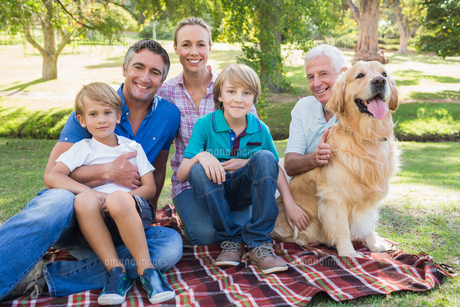 Happy family smiling at the camera with their dogの素材 [FYI00007215]