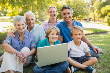 Happy family smiling at camera and using laptop in the parkの写真素材 [FYI00007243]