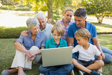 Happy family using laptop in the parkの写真素材 [FYI00007244]