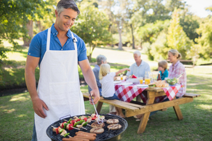 Happy man doing barbecue for his familyの写真素材 [FYI00007255]