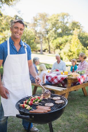 Happy man doing barbecue for his familyの写真素材 [FYI00007257]