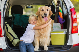 Smiling little girl with her dog in car trunkの写真素材 [FYI00007289]