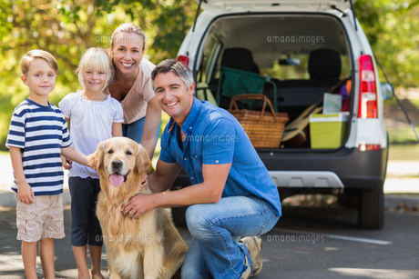 Happy family smiling at the camera with their dogの写真素材 [FYI00007290]