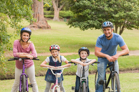 Happy family on their bike at the parkの写真素材 [FYI00007338]