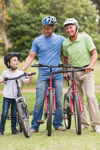 Happy multi generation family on their bike at the parkの写真素材 [FYI00007350]
