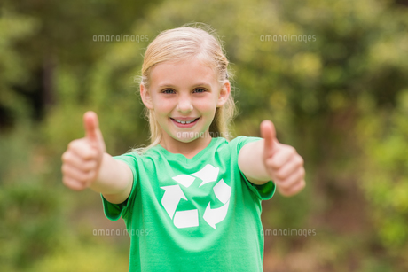Happy little girl in green with thumbs upの素材 [FYI00007385]