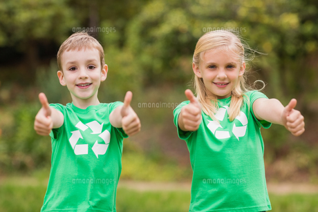 Happy siblings in green with thumbs upの素材 [FYI00007386]