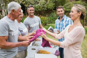 Happy volunteer family separating donations stuffsの素材 [FYI00007420]
