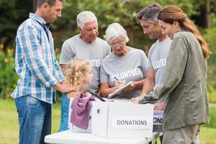 Happy volunteer family separating donations stuffsの素材 [FYI00007424]