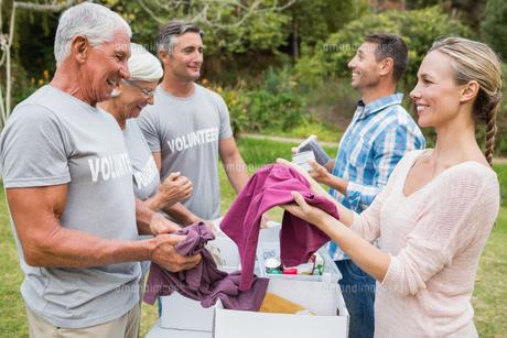 Happy volunteer family separating donations stuffsの素材 [FYI00007425]