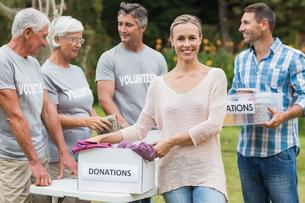 Happy volunteer family separating donations stuffsの素材 [FYI00007428]
