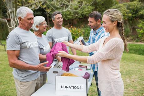 Happy volunteer family separating donations stuffsの素材 [FYI00007429]