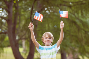 Young boy holding an american flagの写真素材 [FYI00007448]