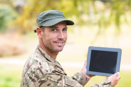 Soldier looking at tablet pc in parkの写真素材 [FYI00007457]