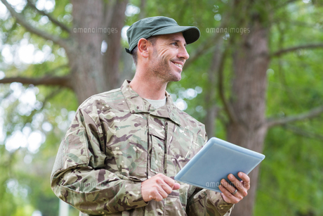 Soldier looking at tablet pc in parkの写真素材 [FYI00007459]