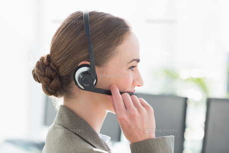 Smiling businesswoman with headset using computersの素材 [FYI00007465]