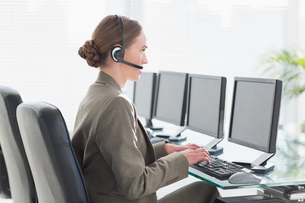 Smiling businesswoman with headset using computersの素材 [FYI00007466]