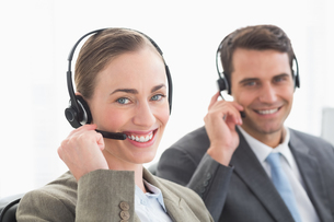 Business people with headsets smiling at cameraの写真素材 [FYI00007470]