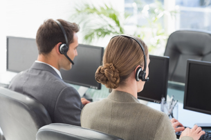Business people with headsets using computersの写真素材 [FYI00007471]