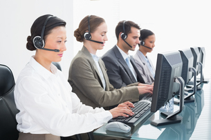Business people with headsets using computersの写真素材 [FYI00007474]