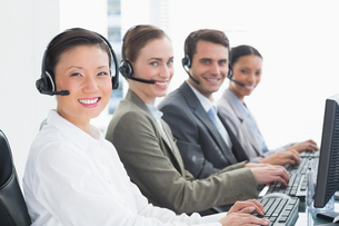 Business people with headsets using computersの写真素材 [FYI00007475]