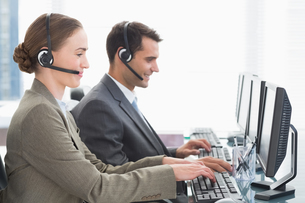 Business people with headsets using computersの写真素材 [FYI00007476]