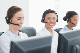 Business people with headsets smiling at cameraの写真素材 [FYI00007479]